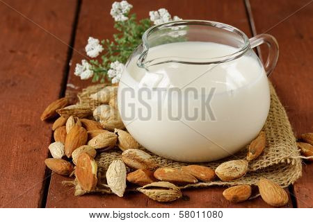 almond milk in a glass jug with whole nuts