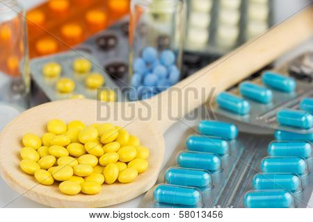 spoon with pills and tablets in a blister pack and a glass jar