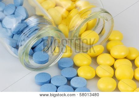 Two glass jars with pills blue and yellow