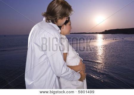 Expectant Couple On Beach Looking At  Sunrise