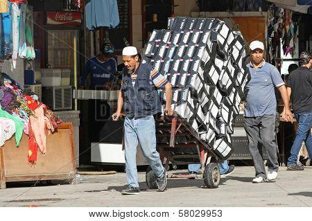 Men Pushing A Trolley