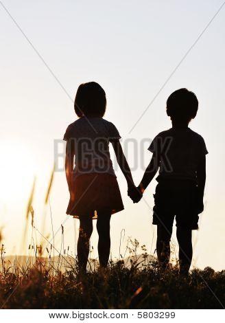 Two children sunset romantic scene