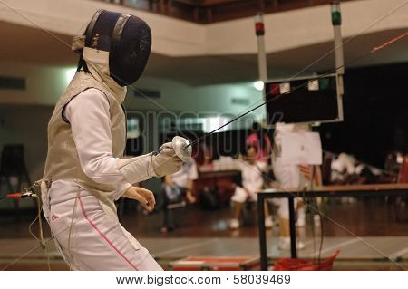 Foil swordman fighting in fencing match
