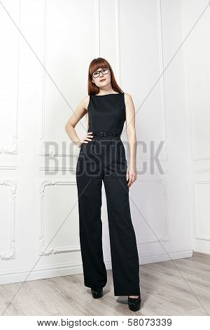 Portrait of beautiful woman with red hair in black glasses and black suit