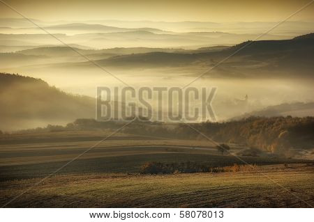 Autumn morning landscape with fog trough hills and meadow