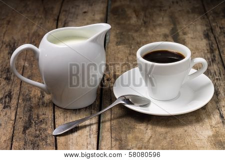 Coffee. Cup Of Coffee With Milk Jug On Wood Background.