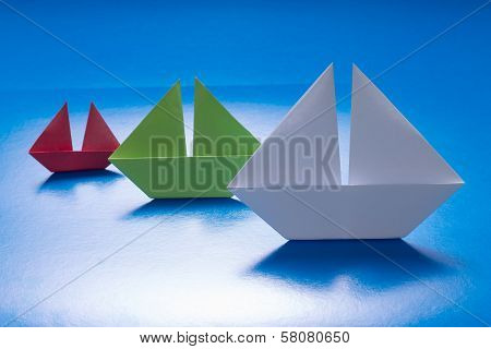 Group Of Paper Ships Sailing On Blue Paper Sea. Origami Boat. Paper Sea
