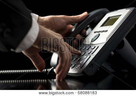 Businessman Dialling Out On A Telephone Call