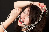 stock photo of sado-masochism  - beautiful young woman with a chain around his neck on a black background - JPG