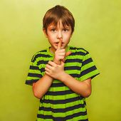 boy holding finger to his mouth silence requested quiet