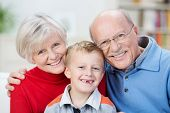 stock photo of grandparent child  - Beautiful family portrait showing the generations with a cute little boy with his front teeth missing sitting with his happy smiling grandparents in a close embrace - JPG