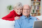 picture of wifes  - Friendly senior couple with happy contented smiles posing together in their living room with the husband sitting using a tablet on the sofa as his wife hugs him from behind - JPG