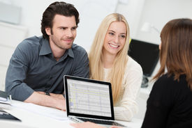 image of conduction  - Investment or insurance broker or adviser conducting an interview with a smiling young couple as they plan their future investments - JPG