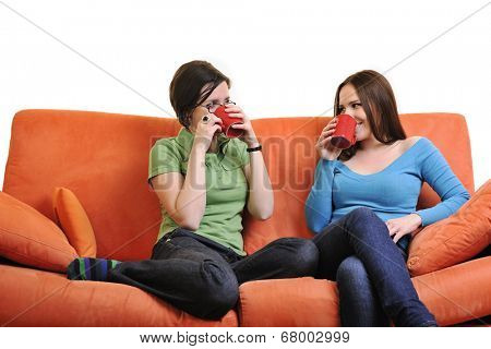 two young woman isolated on white with cup off coffee talking and chating isolated on whtie on orange sofa