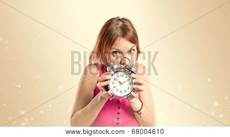 Serious Redhead Girl Holding A Clock Over Ocher Background