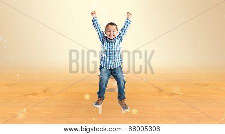 Lucky Boy On A Wooden Chair Over Ocher Background