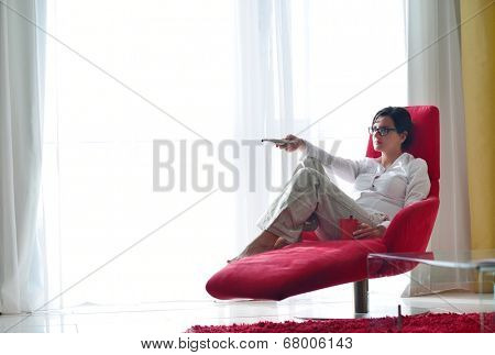 happy young woman watching tv at modern home livingroom