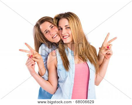 Friends Doing Victory Gesture Over White Background