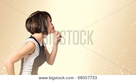 Woman Doing Silence Gesture Over Ocher Background