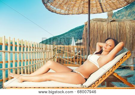 Brown-haired beautiful girl on a lounger