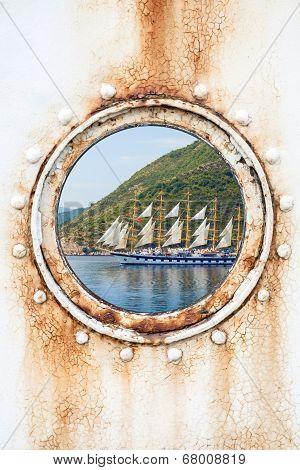 Big Sailing Ship Behind Round Rusted Porthole On White Wall