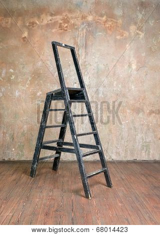 Stepladder In A Room With Hardwood Floors Around A Shabby Wall