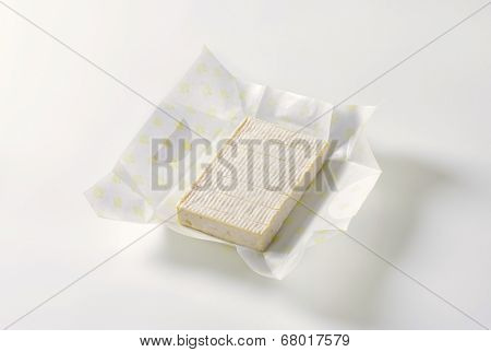 block of surface ripened cow's milk cheese, wrapped in a paper