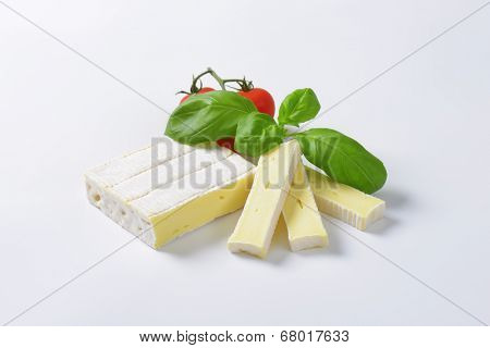 block of surface ripened cow's milk cheese with tomatoes and basil