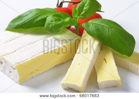 detail of cow's milk cheese with surface mold, accompanied with tomato and basil