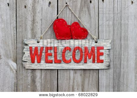 Rustic wood welcome sign with red hearts hanging on wooden door