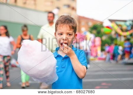 Cute kid eating cotton candy over fair background