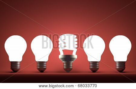 Glowing Spiral Light Bulb In Row Of Tungsten Ones On Red