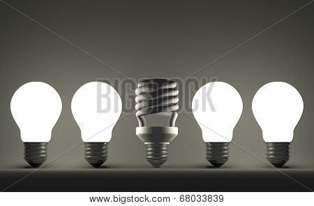 Dead Spiral Light Bulb In Row Of Glowing Tungsten Ones On Gray