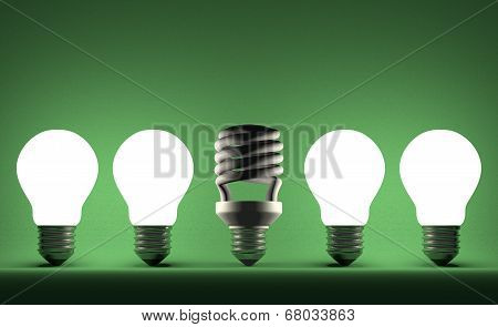 Dead Spiral Light Bulb In Row Of Glowing Tungsten Ones On Green