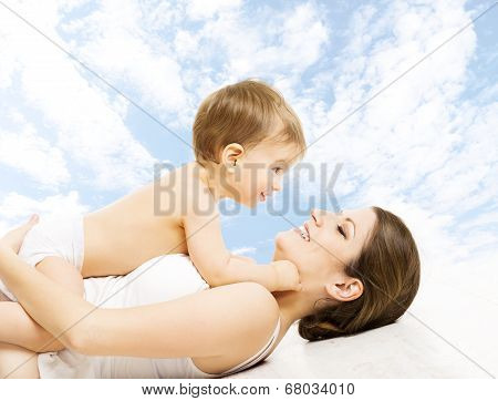 Mother Baby Happy Playing. Child In Diaper Embracing Mama Over Sky Background