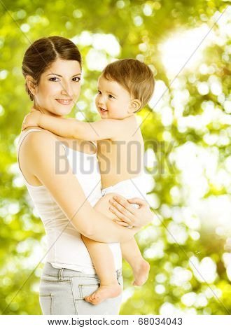 Mother Baby Happy Smiling. Child In Diaper Embracing Mama Over Green Abstract Background