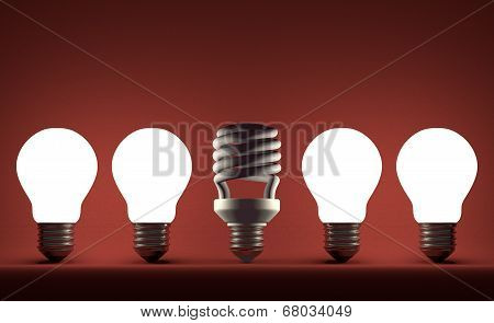 Dead Spiral Light Bulb In Row Of Glowing Tungsten Ones On Red