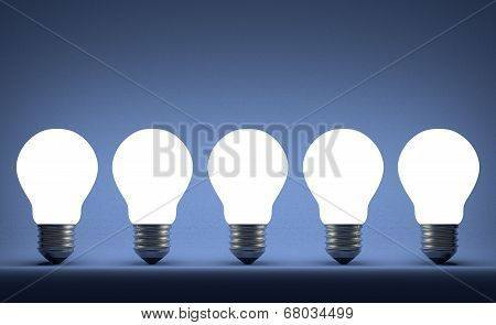 Row Of Glowing Tungsten Light Bulbs On Blue