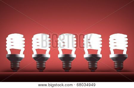 Row Of Glowing Spiral Light Bulbs On Red
