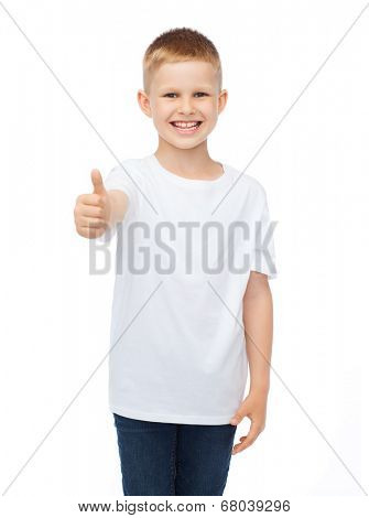 t-shirt design, childhood and happy people concept - smiling little boy in blank white t-shirt showing thumbs up