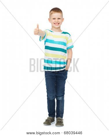 happiness, childhood, gesture and people concept - smiling little boy in casual clothes showing thumbs up