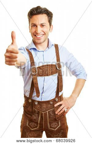 Happy bavarian man in leather pants holding his thumbs up