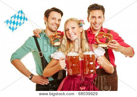 Smiling woman at Oktoberfest carrying two beer glasses in front of two men