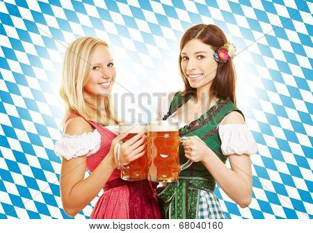 Two smiling women with beer at Oktoberfest in front of bavarian flag