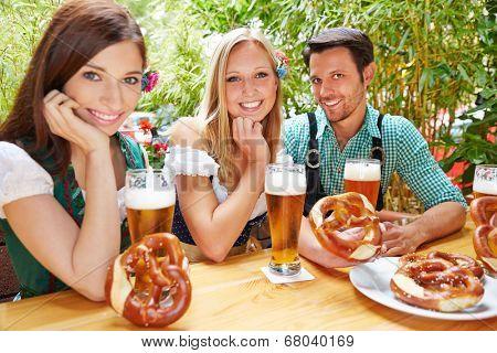 Happy friends sitting in beer garden in Bavaria with pretzel