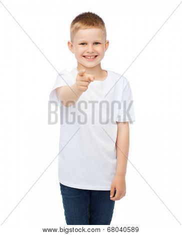 gestures, advertisement, childhood and happy people concept - happy little boy in blank white t-shirt pointing at you