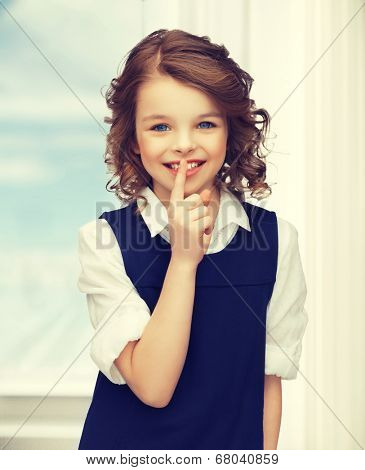 picture of beautiful pre-teen girl showing hush gesture
