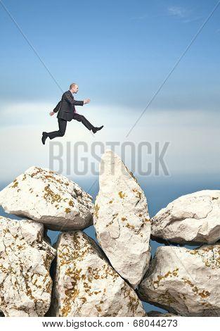 businessman jump over huge rock