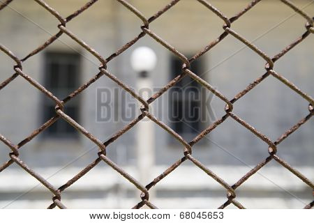 Rustic Metal Chainlink Fence With A Window And Light Pole In Background