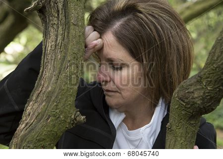 Depressed Middle Age Woman In Forest Leaning On A Tree